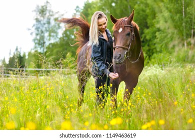 Happy woman feeding her arabian horse with snacks in the field