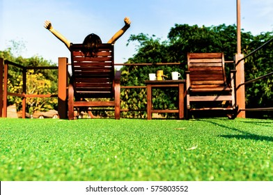 happy woman feel comfortable and relaxing on wooden sun bed furniture outdoor on green artificial grass and looking the blue sky background, coffee morning concept