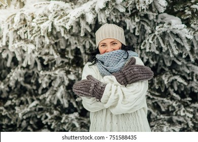 Happy woman feeling cold in winter. Portrait of a cheerful woman hugging herself in front of trees covered in snow.