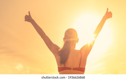 Happy woman feeling free with her thumbs up against golden sunny sky. People happiness, and feeling inspired concept.