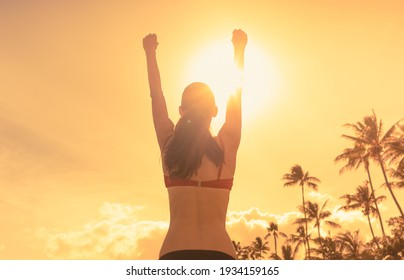 Happy woman feeling strong and free on the beach.Success and life goals concept. Strong and confident woman with arms in the air.