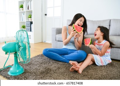 happy woman and female children holding watermelon with blowing electric fan cool wind at summer season and looking each other.
