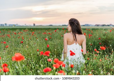 Happy woman in the field of red poppies