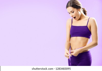 Happy woman in fitness wear with tape, with copyspace for some text, advertising or slogan, against pink background