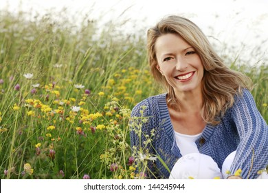 Happy woman with a flower relaxes in the grass with a flower