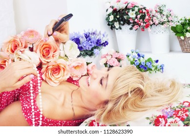 Happy woman with flowers texting message on phone