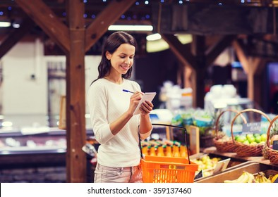 happy woman with food basket and notepad in market