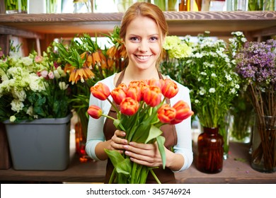 Happy woman with fresh red tulips looking at camera in her shop