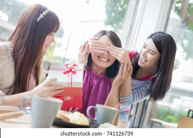 happy woman friends feel surprise with gift in restaurant