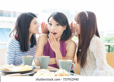 happy woman friends sitting and talking smoething in restaurant