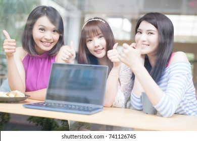happy woman friends thumb up with laptop in restaurant