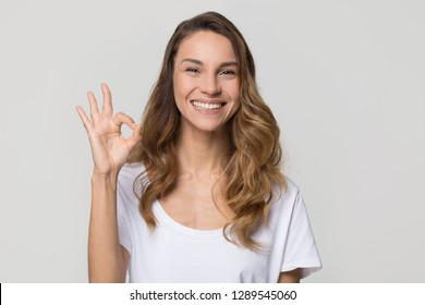 Happy woman gesturing ok smiling with white teeth looking at camera isolated on studio blank background, pretty girl hand showing okay sign satisfied with dental orthodontic service concept, portrait