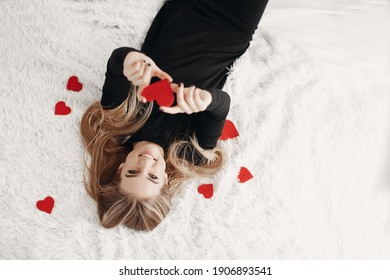 Happy woman with gift and hearts at valentine's day