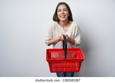 Happy woman giving empty shopping basket, looking at camera smiling. Buyer, e-commerce concept.