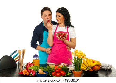 Happy woman giving to her husband to eat strawberry in their kitchen against white background