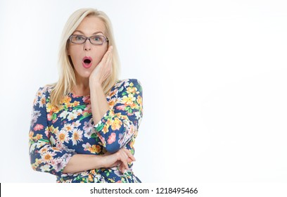 Happy Woman with glasses and surprised shouts holds cheeks by hand. Beautiful woman with blond hair pointing to look. Presenting your product. Expressive facial expressions middle aged woman.