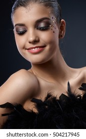 Happy woman with glittering extravagant makeup posing with black boa, smiling.
