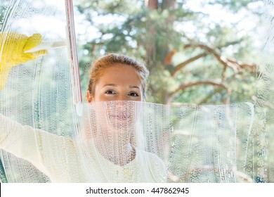 Happy woman in gloves cleaning window with rag and sponge at home. Large window glass in foam. Beautiful view with green forest. Housework concept.