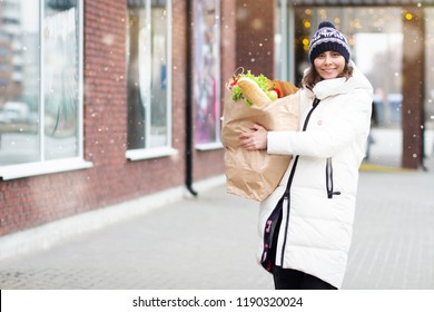 Happy woman goes with paper bag of vegetables and food from grocery store. Preparing for winter celebrations Christmas and New Year. Girl with paper package of food on street.