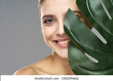 A happy woman with a green palm leaf in front of her eyes is smiling at the camera Close-up cropped view