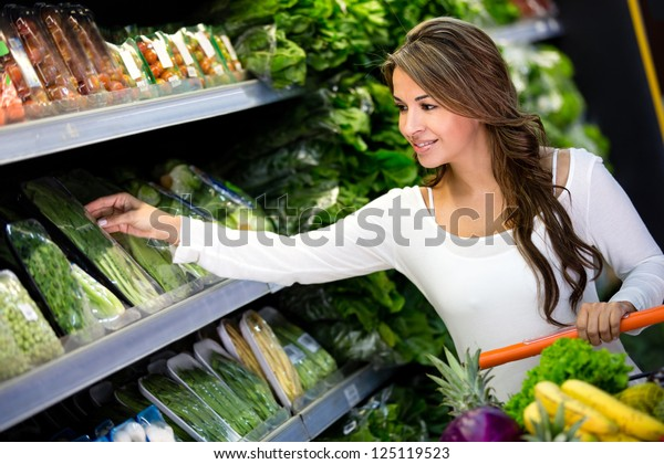 Happy woman grocery shopping at the supermarket