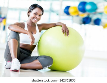 Happy woman at the gym with a Pilates ball and smiling