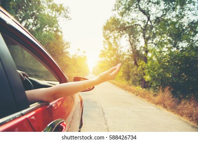 Happy woman hand out window car red with sunlight