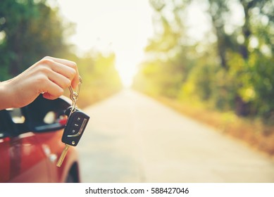 Happy woman hand out window car red and car key with sunlight