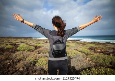 Happy woman with hands up enjoy ocean beach, Lanzarote, Canary Island, Spain. Summer vacation concept. Travel destination. Back view