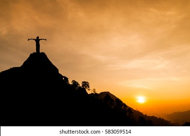 Happy woman with hands up on the top of the mountain with sunrise. Success concept