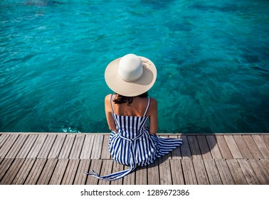Happy woman in hat relaxing on sea pier in Sardinia island, Italy. Summer vacations concept