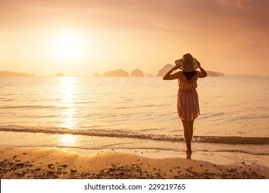 Happy Woman in a hat and short dress enjoys in Sea Sunset. In the background hilly karst mountains to the sea,  vintage color