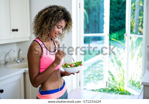 Happy woman having bowl of salad while listening to music in kitchen