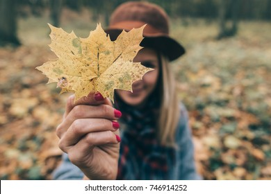 Happy woman having fun with leaves outdoor in forest
