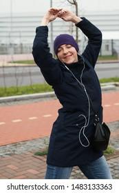 Happy woman in headphones dancing in the street