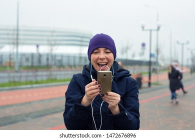 Happy woman in headphones holds a phone in the city