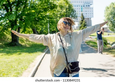 Happy Woman with headphones listening to music on the street