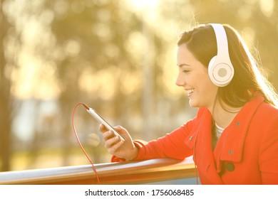 Mujer feliz con auriculares escucha música en un teléfono inteligente en un balcón al atardecer
