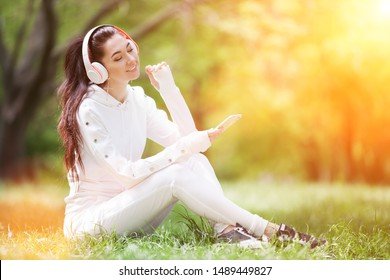 Happy woman with headphones relaxing in the sunny park. Beauty nature scene with colorful background. Fashion woman enjoying the music from her mobile phone in summer season. Outdoor lifestyle