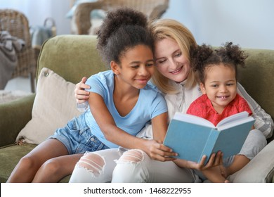 Happy woman with her African-American daughters reading book at home
