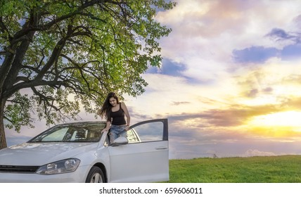 Happy woman with her car at sunset - Attractive young brunette enjoys her car, in the spring nature as the sun is setting down.