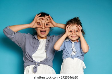 Happy woman and her cute daughter looking at camera through their fingers in ok gesture, imitating binoculars. Copy space, blue background.