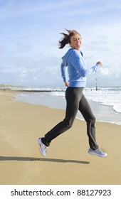 A happy woman in her forties jogging on a beautiful sandy beach and wearing a blue hooded top.