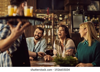 Happy woman and her friends communicating with a waiter and having fun in a pub.