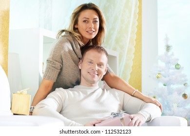 Happy woman and her husband having rest at home on Christmas day