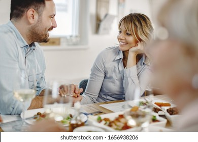 Happy woman and her husband holding hands while communicating during lunch in dining room.