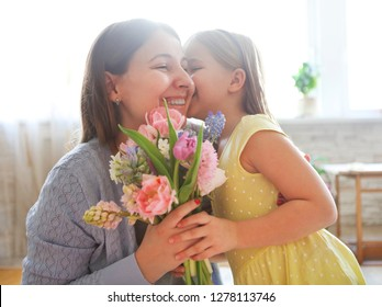 Happy woman and her little daughter in the living room. Mother day concept