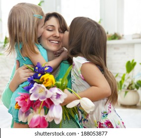 Happy woman and her little daughters in the living room. Mother day concept