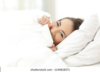 Happy woman hiding face under the bed sheet at home