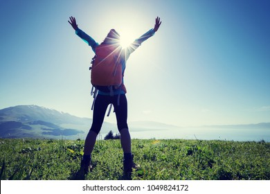 happy woman hiker on beautiful green mountain hill top